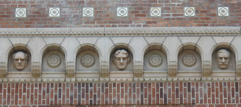 Photo of stone heads atop the University of Oregon Library