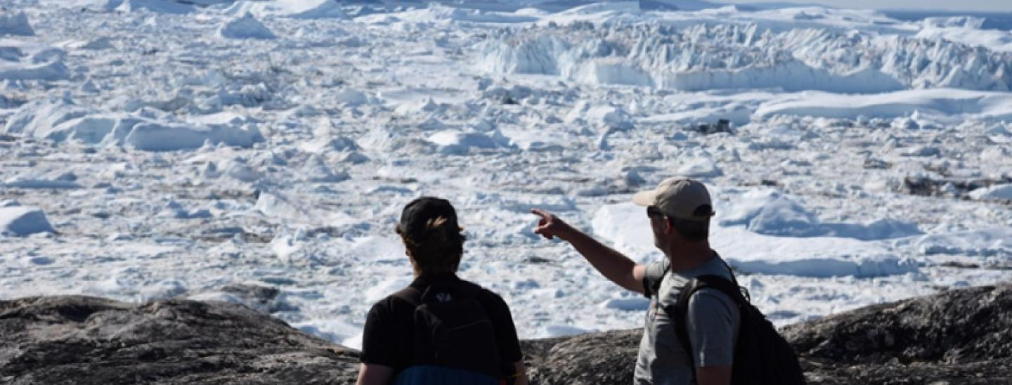 picture of a two people standing by a glacier